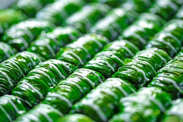 Groen gekleurde turkse dessertbaklava in rijen geplaatst