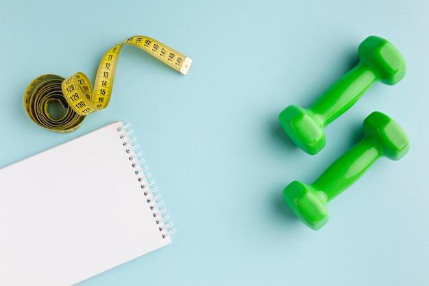 Groen gewichten en notitieboekje op blauwe achtergrond