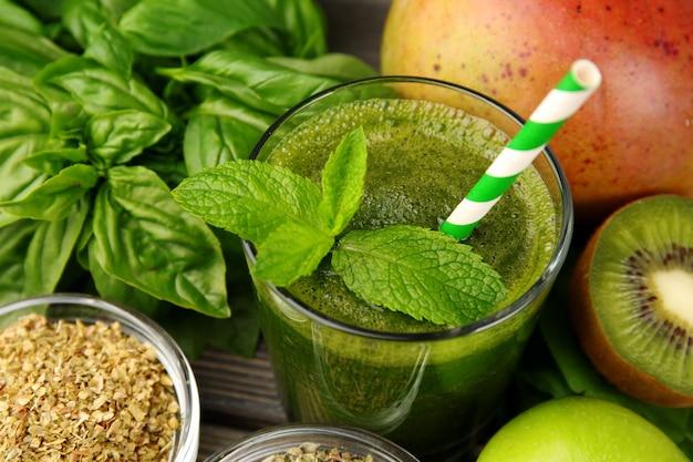 Groen gezond sap met fruit en kruiden op tafel