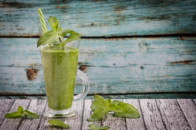 Groen gras smoothie in een glas op de tafel