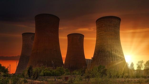 Groen grasveld dichtbij elektrische centrale tijdens zonsondergang