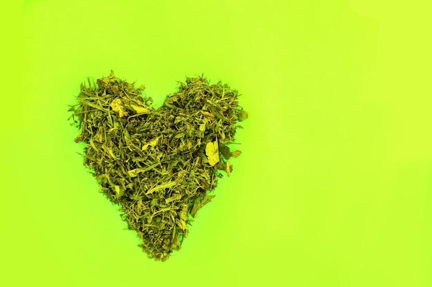 Groen hart gemaakt van vers gras op heldere kleurrijke achtergrond.