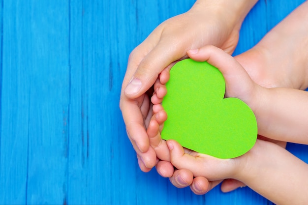 Groen hart in handen van volwassene en kind.