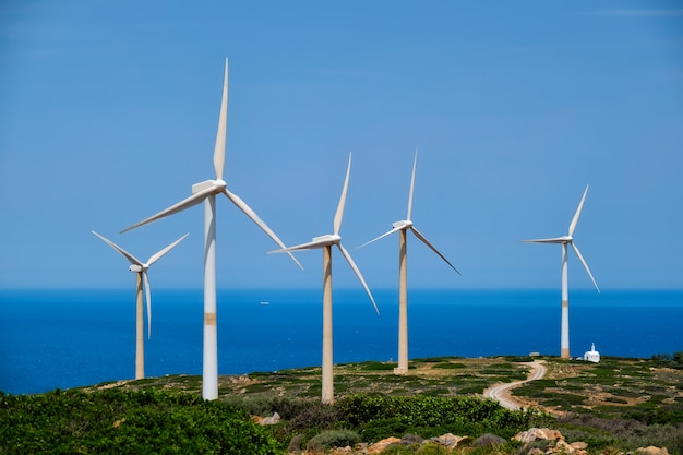Groen hernieuwbaar alternatief energieconcept - windturbines die elektriciteit opwekken. windpark op kreta, griekenland met kleine witte kerk