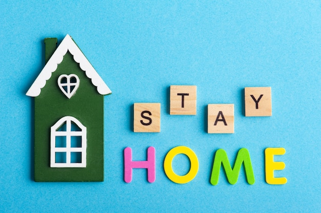 Groen houten huis en stay home-teken