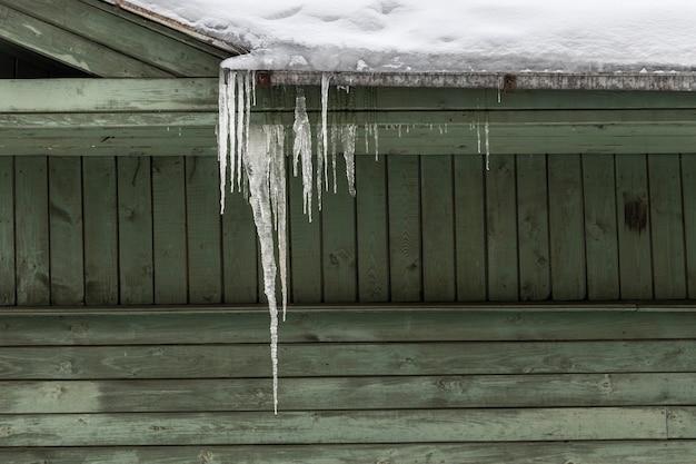 Groen houten huis met hangende ijspegel. hoge kwaliteit foto