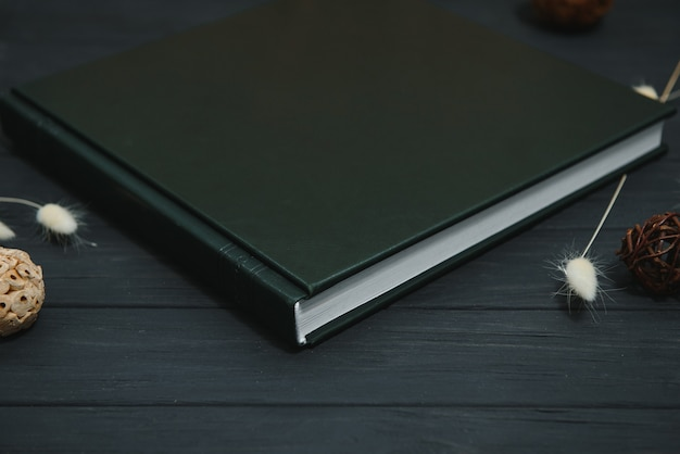 Groen huwelijks- of familiefotoboek met leren kaft.