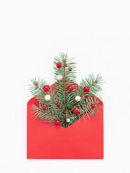Groen kerstboomsymbool in rode envelop op witte exemplaar ruimteachtergrond.