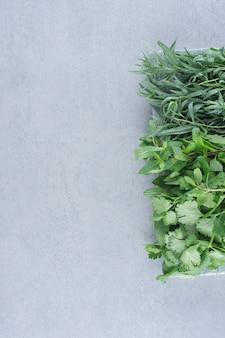 Groen kruidenassortiment op een grijze steenachtergrond.