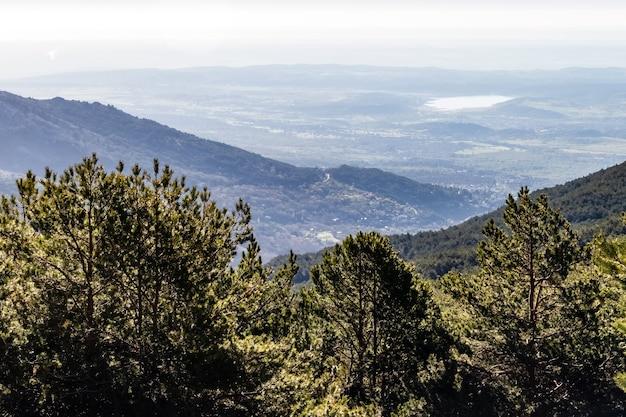 Groen landschap bij zonsopgang boven de vallei, met bomen, rotsen en verre uitzicht op bergen aan de horizon. la morcuera, navacerrada, madrid. europa.