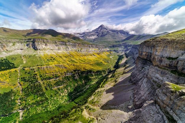 Groen landschap in de pyreneeën van de ordesa en monte perdido vallei met bergen, rotsen, bossen en lucht met wolken. luchtfoto boven.