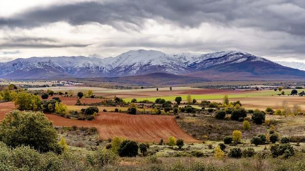 Groen landschap met besneeuwde bergen en dramatische hemel in somosierra madrid. europa.