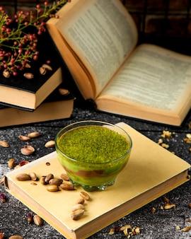 Groen lichtdessert dat met geraspte pistaches wordt bestrooid