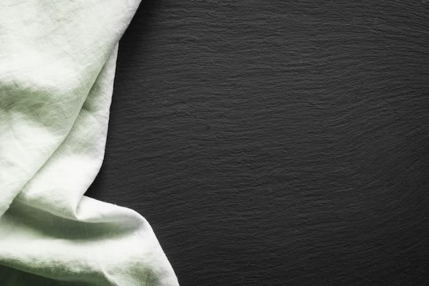 Groen linnenservet op zwarte leischotel.