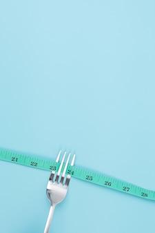 Groen meetlint gewikkeld rond mes en vork op blauwe achtergrond
