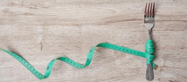 Groen meetlint gewikkeld rond mes en vork op houten tafel achtergrond