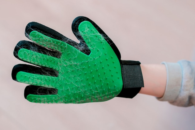 Groen met zwarte rubberen handschoen met spikes en kattenwol. huisdieren schoonmaken. dieren. bruikbaar. doorn