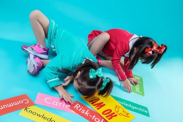 Groen naamplaatje bij zich. donkerharige tweelingzusjes in kleurrijke jurken zitten omringd met verschillende naamplaatjes