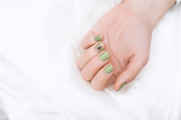 Groen nagelontwerp met zwarte boomkunst op middelvinger. gemanicuurde vrouwelijke hand