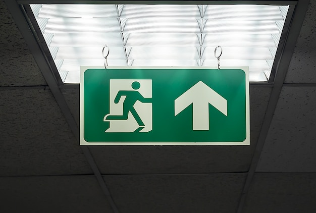 Groen nooduitgangsymbool hangt aan het plafond