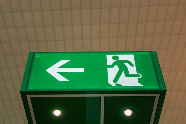 Groen nooduitgangteken dat de weg toont om te ontsnappen.