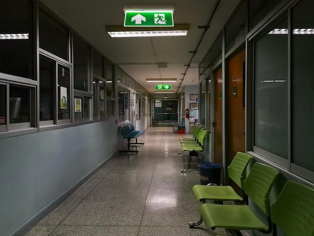 Groen nooduitgangteken in het ziekenhuis dat de manier toont om bij nacht te ontsnappen
