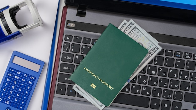 Groen paspoort met amerikaanse dollars op laptoptoetsenbord online registratie omkoping en corruptie