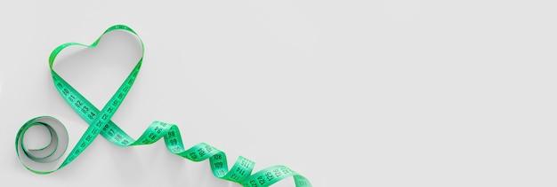 Groen plastic meetlint met metrische schaal in de vorm van een hart op grijze achtergrond. bovenaanzicht, kopieer ruimte. geschiktheidsconcept.