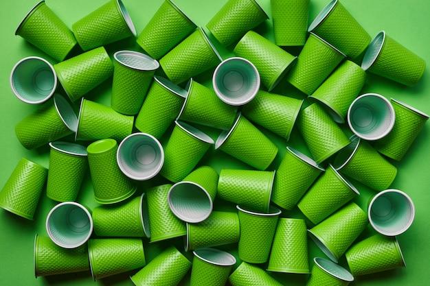 Groen plastic wegwerpservies op groene achtergrond
