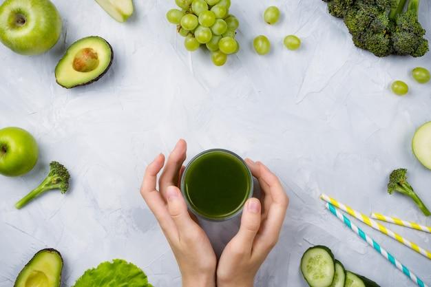 Groen sap, groenten en fruit op grijs