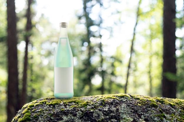 Groen sap in een glazen fles agave limonade in het bos sodawater zoet en zuur met natuurlijke in...