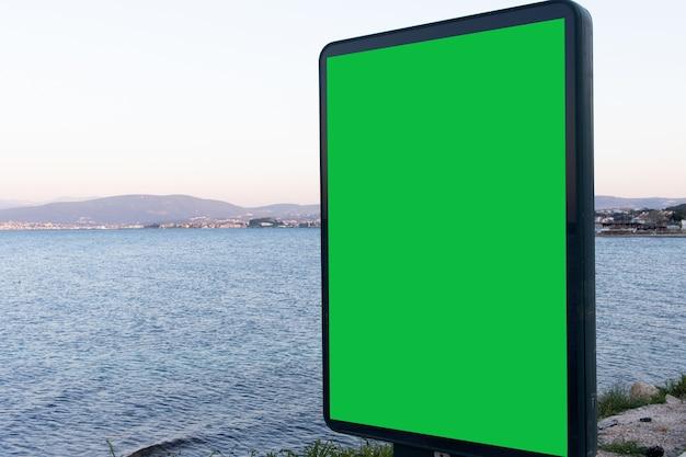 Groen scherm voor advertenties met uitzicht op de oceaan, een uitstekende ruimte voor uw tekst