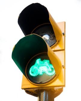 Groen signaal voor fietsen bij gele verkeerslichten tegen witte achtergrond