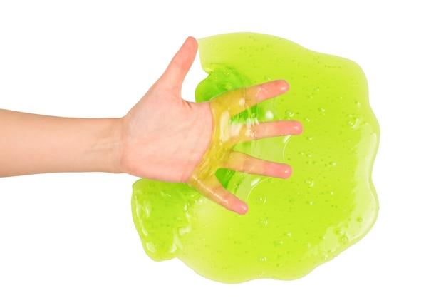 Groen slijmstuk speelgoed in vrouwenhand dat op wit wordt geïsoleerd.