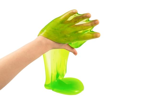 Groen slijmstuk speelgoed in vrouwenhand die op wit wordt geïsoleerd. bovenaanzicht.