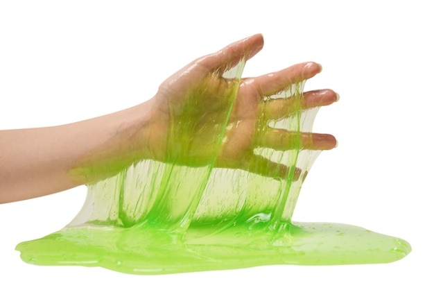 Groen slijmstuk speelgoed in vrouwenhand die op wit wordt geïsoleerd.