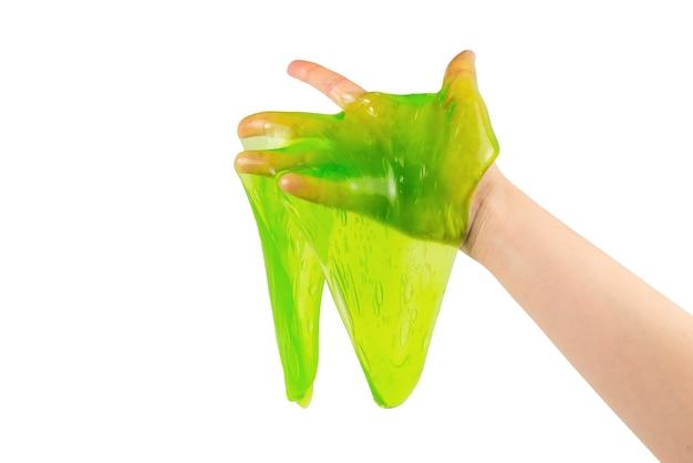 Groen slijmstuk speelgoed in vrouwenhand die op wit wordt geïsoleerd