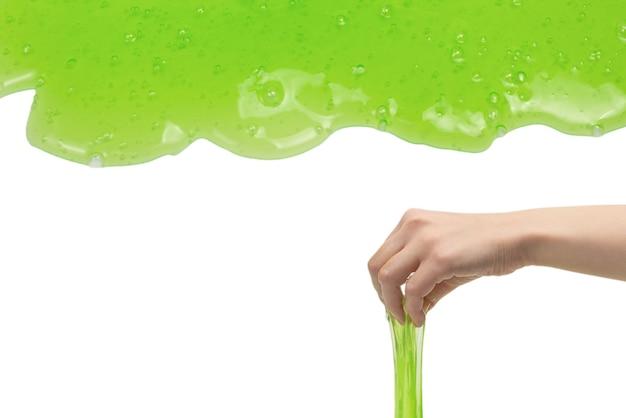 Groen slijmstuk speelgoed in vrouwenhand die op witte achtergrond wordt geïsoleerd.