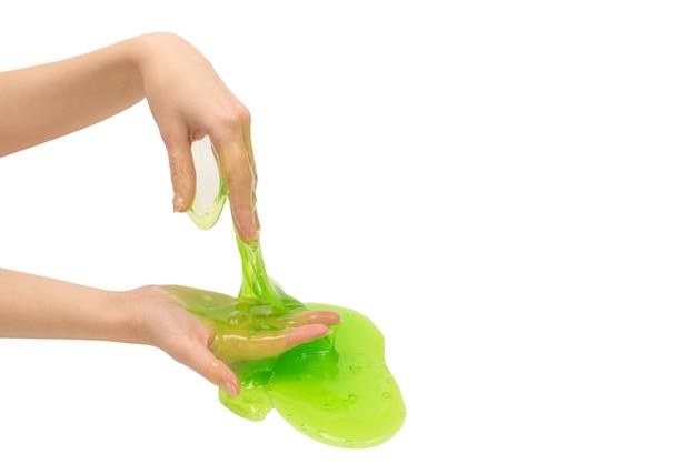 Groen slijmstuk speelgoed in vrouwenhand die op witte oppervlakte wordt geïsoleerd.
