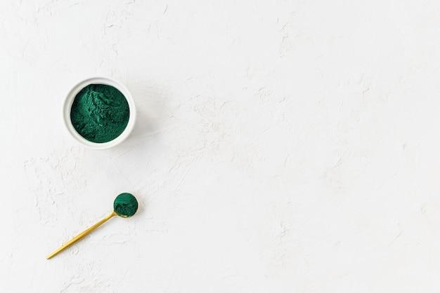 Groen spirulinapoeder in een lepel en kom met exemplaarruimte