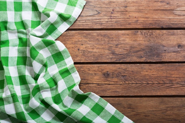 Groen tafelkleed op oude houten tafel, bovenaanzicht