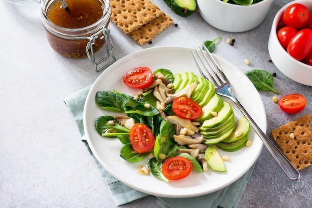 Groen vegetarisch ontbijt in een kom met avocado-champignons, cherrytomaat, pijnboompitten, spinazie en dressing met vinaigrette saus dieet concept van vegetarisch eten