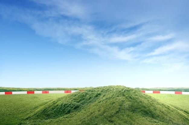 Groen veld met een heuvel van de grond en een blauwe lucht