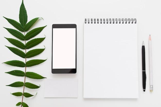 Groen verlof met lege blocnote en smartphone