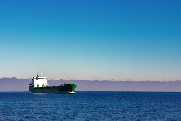 Groen vrachtschip dat zich in stilstaand water van de oostzee beweegt