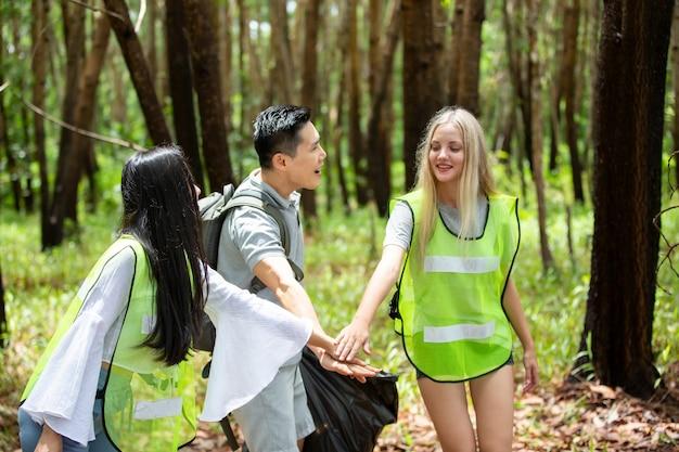 Groen vrijwilligerswerk. optimistische twee vrijwilligers die een vuilniszak vasthouden en helpen bij het opruimen van afval in het park, ze halen het afval op en stoppen het in een zwarte vuilniszak. ecologie bescherming concept.