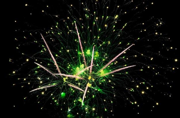 Groen vuurwerk in de lucht op zwarte achtergrond Premium Foto