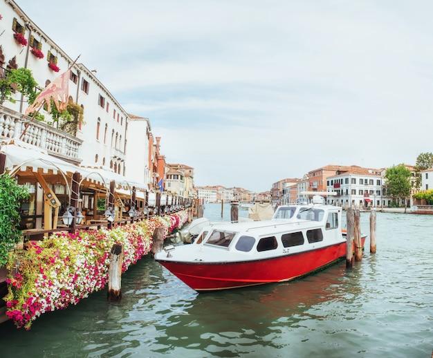Groen waterkanaal met gondels en kleurrijke gevels van oude middeleeuwse gebouwen in de zon in venetië