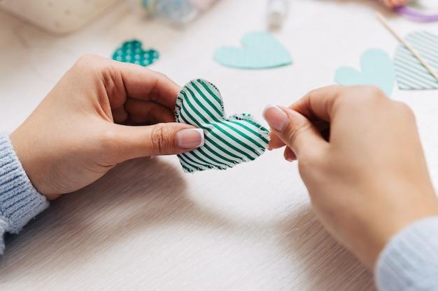 Groen zelfgemaakt hart gemaakt van stof in handen.