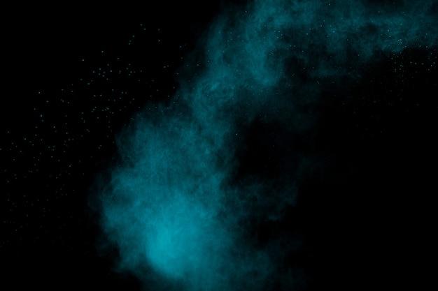 Groenachtig blauwe stofexplosie op zwarte achtergrond
